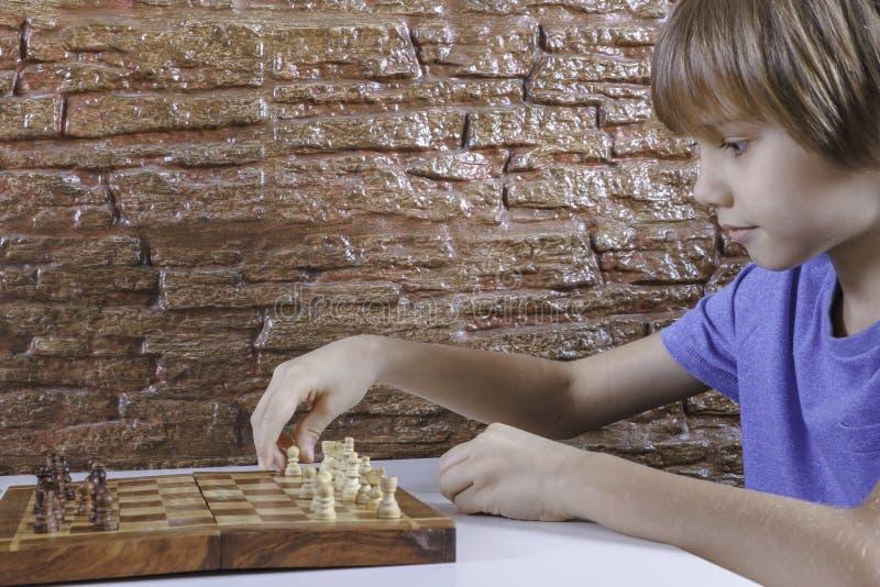 Portret van een weinig Kaukasisch jongen het spelen schaak en het maken van volgende beweging stock foto