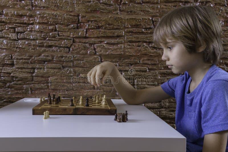 Portret van een weinig Kaukasisch jongen het spelen schaak en het maken van volgende beweging stock afbeeldingen