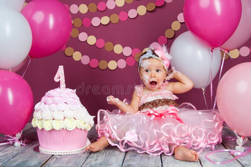 Portret van een weinig vrolijk feestvarken met de eerste cake Het eten van de eerste cake Ineenstortingscake stock afbeeldingen