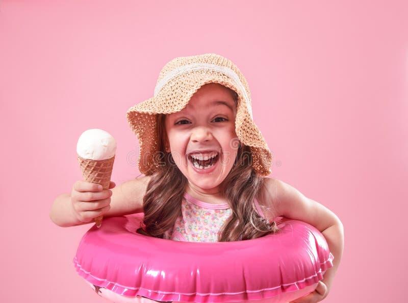 Portret van een weinig vrolijk meisje met roomijs op een gekleurde achtergrond royalty-vrije stock foto