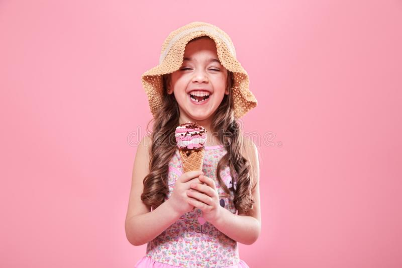 Portret van een weinig vrolijk meisje met roomijs op een gekleurde achtergrond stock fotografie