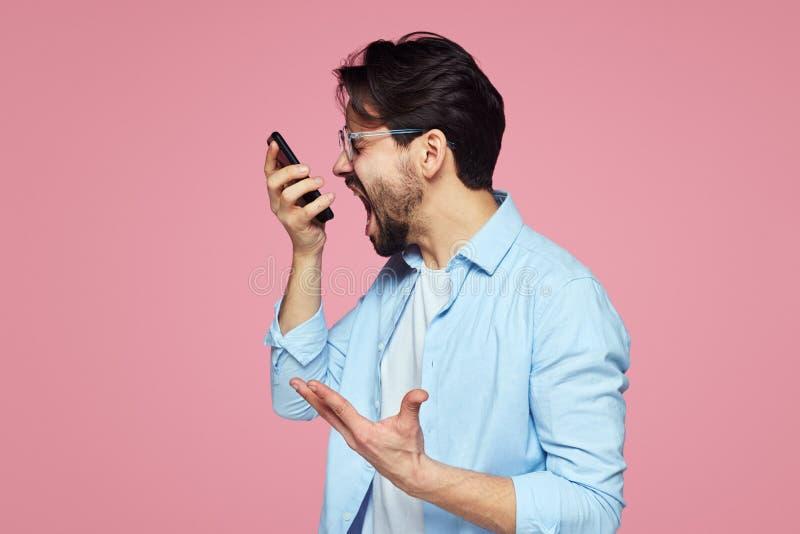 Portret van een woedende jonge zakenman die bij mobiele telefoon schreeuwen die over roze achtergrond wordt geïsoleerd royalty-vrije stock afbeeldingen