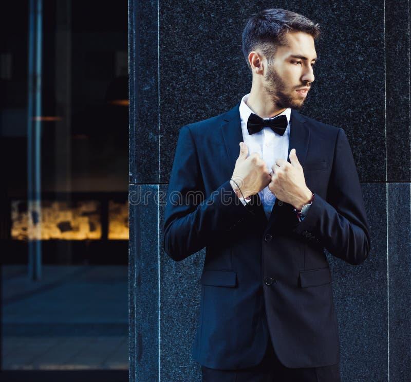 Portret van een zakenman in een kostuum, een vlinderdas en zonnebril hipster stock afbeeldingen