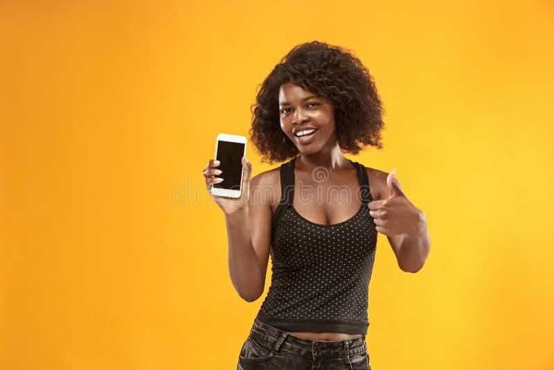 Portret van een zeker toevallig afromeisje die het lege scherm mobiele telefoon tonen royalty-vrije stock fotografie