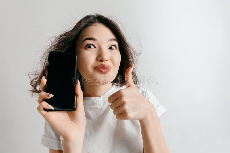 Portret van een zeker toevallig Aziatisch meisje die het lege scherm van mobiele telefoon tonen stock afbeeldingen