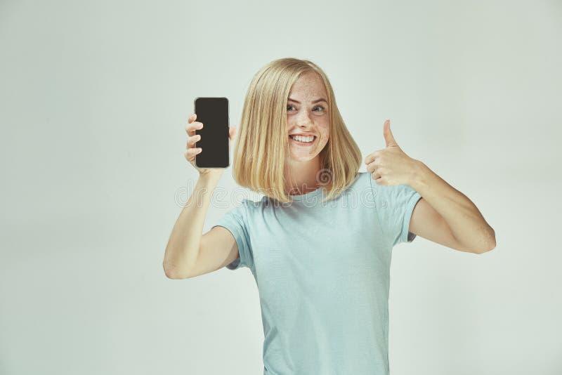 Portret van een zeker toevallig meisje die het lege scherm mobiele die telefoon tonen over grijze achtergrond wordt geïsoleerd royalty-vrije stock afbeeldingen