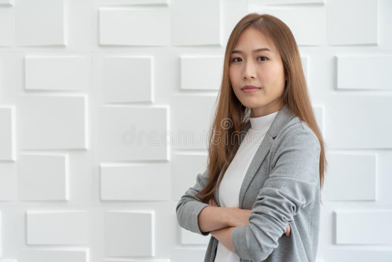 Portret van een zekere Aziatische bedrijfsvrouw die zich over wit bevinden stock foto