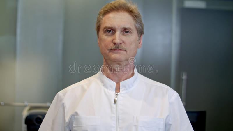 Portret van een zekere hogere arts die zich bij het ziekenhuis bevinden terwijl het bekijken camera stock afbeeldingen