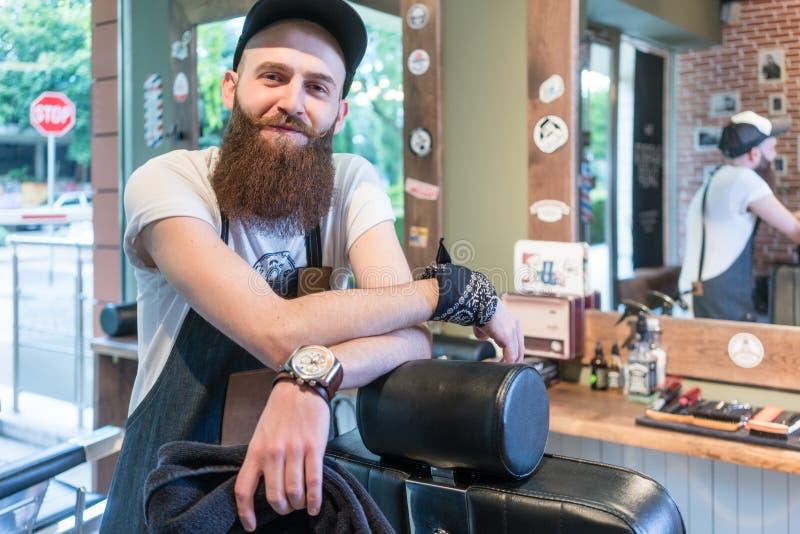Portret van een zekere jonge kapper die in een uitstekende schoonheidssalon glimlachen royalty-vrije stock afbeeldingen