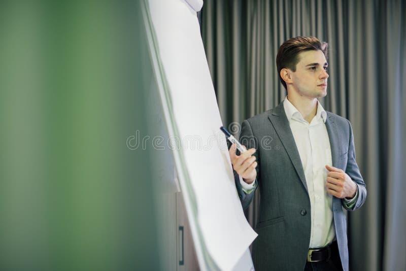 Portret van een zekere zakenman die presentatie op flipchart in modern bureau maken royalty-vrije stock afbeelding