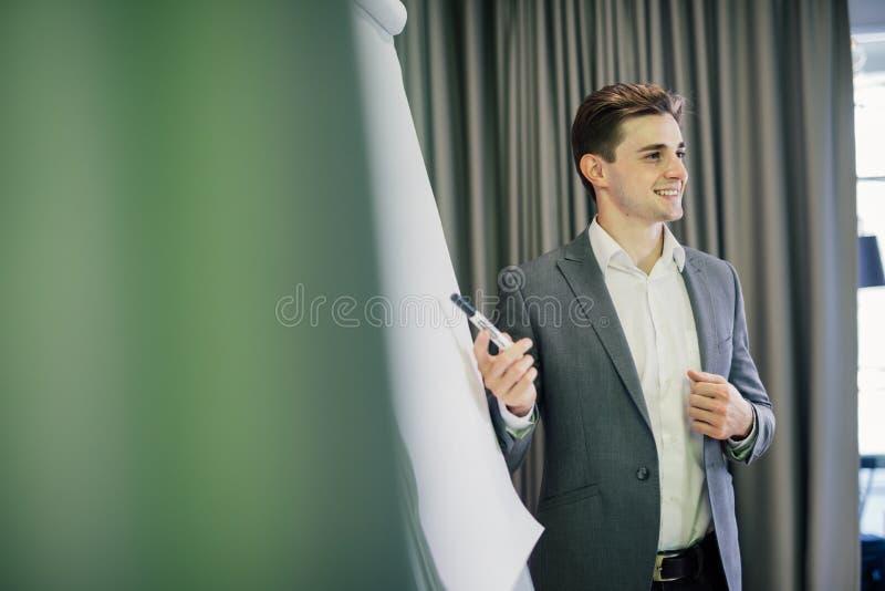 Portret van een zekere zakenman die presentatie op flipchart in modern bureau maken stock foto