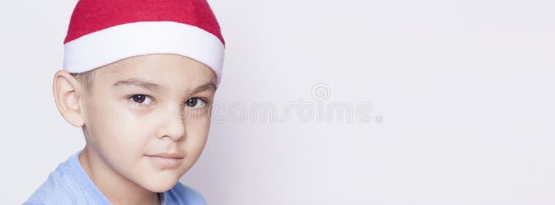Portret van een zes-jaar-oude jongen tegen de witte achtergrond Het vieren Kerstmis 6-7 éénjarigenjong geitje met Kerstmanhoed stock fotografie