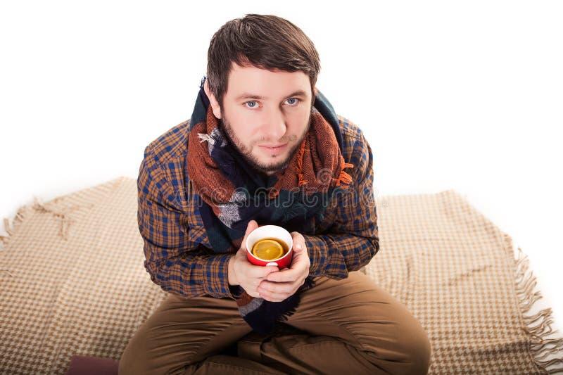 Portret van een zieke mens met de griep die en een warme theekop houdt hoest stock afbeeldingen