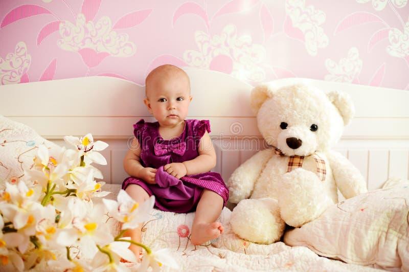 Portret van een zoet babymeisje met haar beer stock afbeeldingen