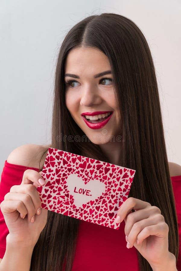 Portret van een zoet perfect meisje die bij camera met hart gevormd document in haar handen glimlachen De Dag van Valentine ` s o stock fotografie
