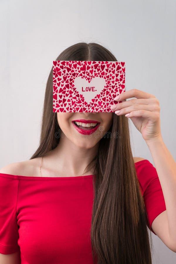 Portret van een zoet perfect meisje die bij camera met hart gevormd document in haar handen glimlachen De Dag van Valentine ` s o royalty-vrije stock foto's