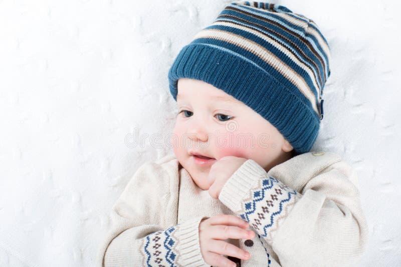 Portret van een zoete baby in een warme gebreide hoed en een sweater stock fotografie