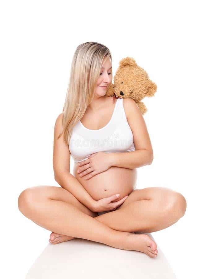 Portret van een zwangere vrouwenzitting op vloer en holdingsbuik stock foto