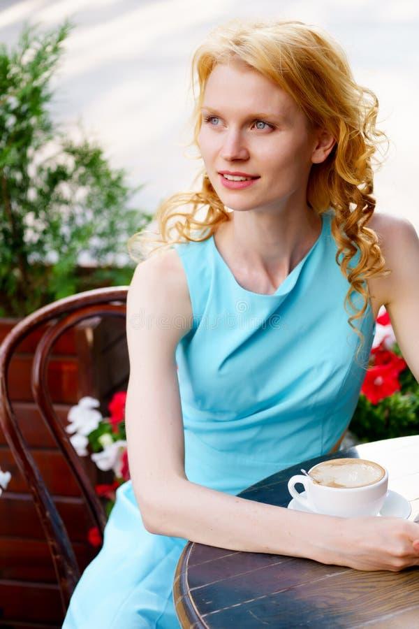 Portret van elegante jonge vrouwenzitting bij lijst in koffie royalty-vrije stock afbeelding