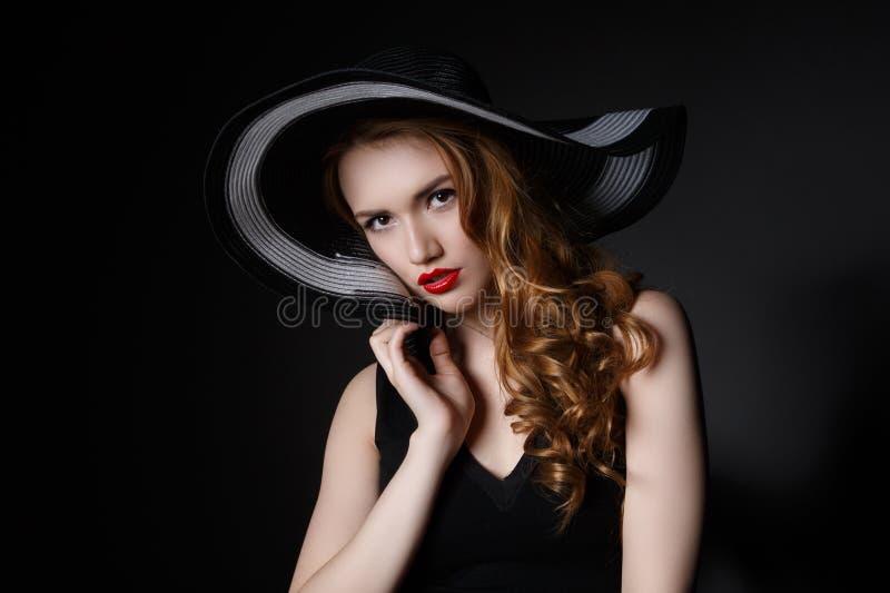 Portret van elegante vrouw in zwarte hoed en kleding stock fotografie