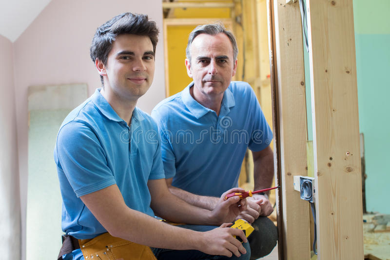 Portret van Elektricien With Apprentice Working in Nieuw Huis stock foto's