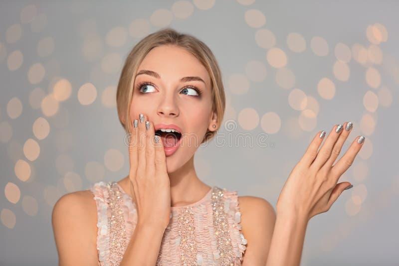 Portret van emotionele jonge vrouw met glanzende manicure op vage achtergrond royalty-vrije stock foto