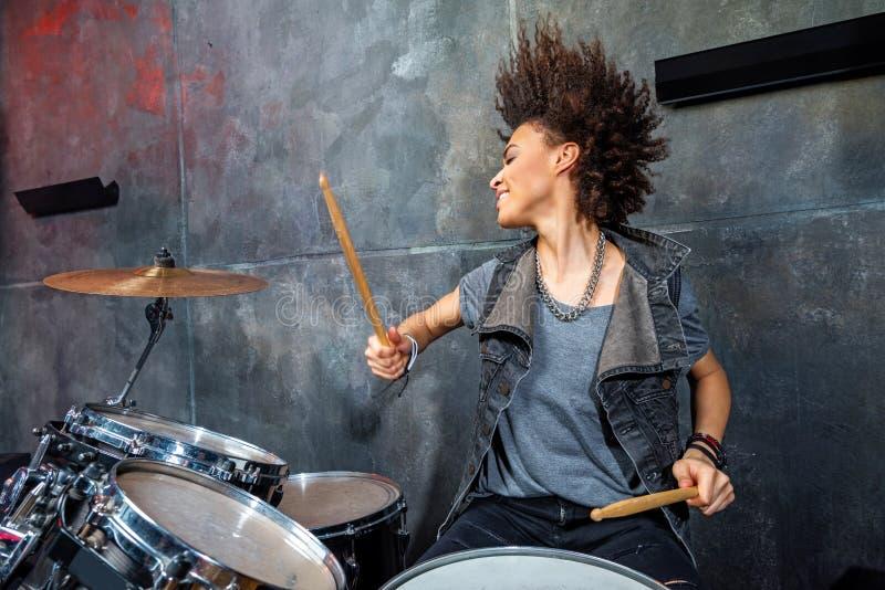 Portret van emotionele vrouw het spelen trommels in studio stock afbeeldingen