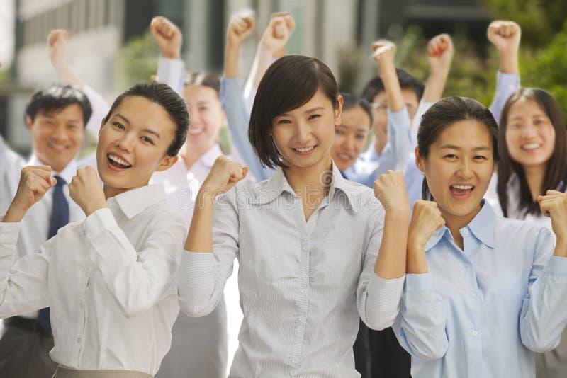 Portret van enthousiaste en opgewekte groep bedrijfsmensen die met omhoog vuisten toejuichen stock afbeelding