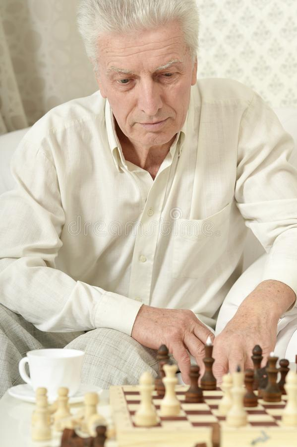 Portret van ernstig hoger mens het spelen schaak thuis royalty-vrije stock afbeeldingen