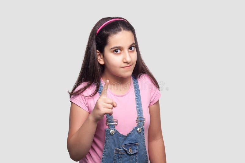Portret van ernstig mooi donkerbruin jong meisje in toevallige stijl, roze t-shirt en blauwe denimoverall status, die eruit zien  stock afbeeldingen
