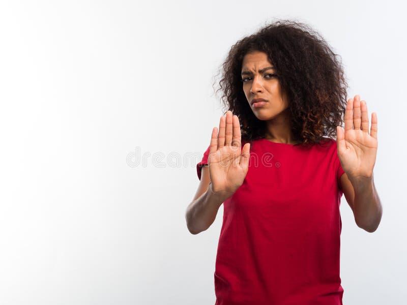 Portret van ernstige jonge Afrikaanse vrouw in rode t-shirt die eindegebaar met haar die palmen tonen over witte muur wordt geïso stock fotografie