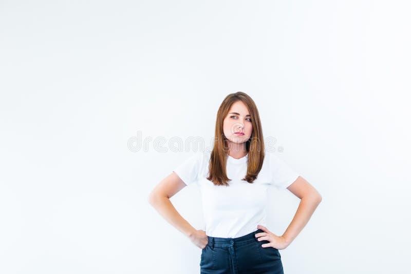 Portret van ernstige jonge Kaukasische, donkerbruine vrouw die in witte T-shirt boos en gefrustreerd geïsoleerd op witte achtergr royalty-vrije stock foto