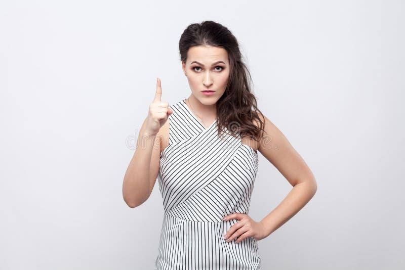 Portret van ernstige mooie jonge donkerbruine vrouw met make-up en gestreepte kleding die zich met waarschuwingsbord bevinden en  stock afbeeldingen