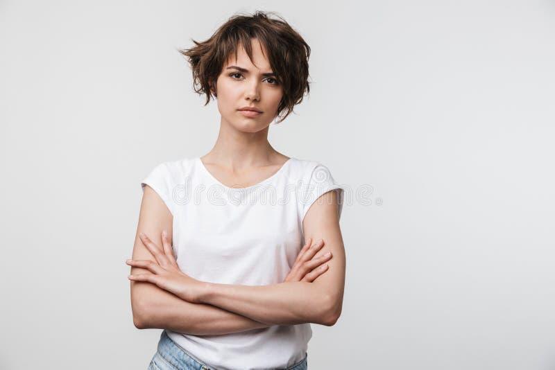 Portret van ernstige vrouw met kort bruin haar in basist-shirt die en camera fronsen bekijken royalty-vrije stock afbeelding
