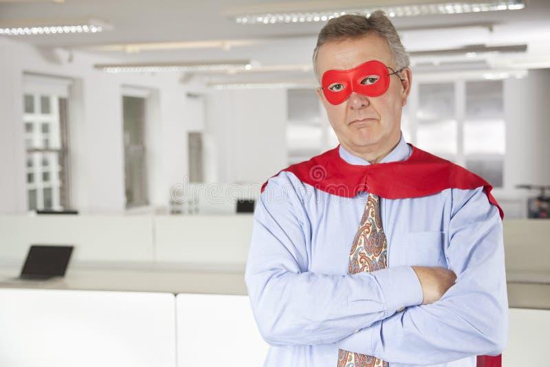 Portret van ernstige zakenman in superherokostuum in bureau royalty-vrije stock afbeelding