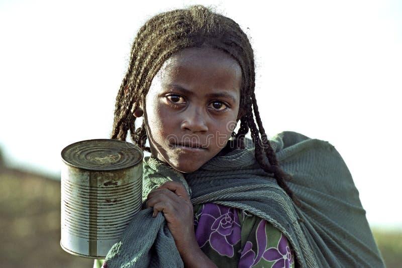 Portret van Ethiopisch meisjes halend water stock foto's