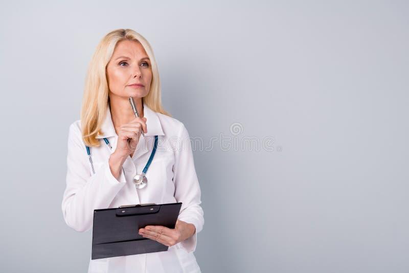 Portret van expert doc gepensioneerde gepensioneerde vrouw heeft raadpleging van het corona-virus, schrijf het recept klembord en royalty-vrije stock afbeelding