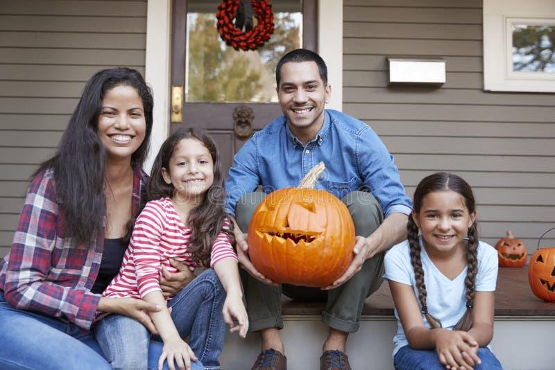 Portret van Familie die Halloween-Pompoen op Huisstappen snijden stock afbeelding