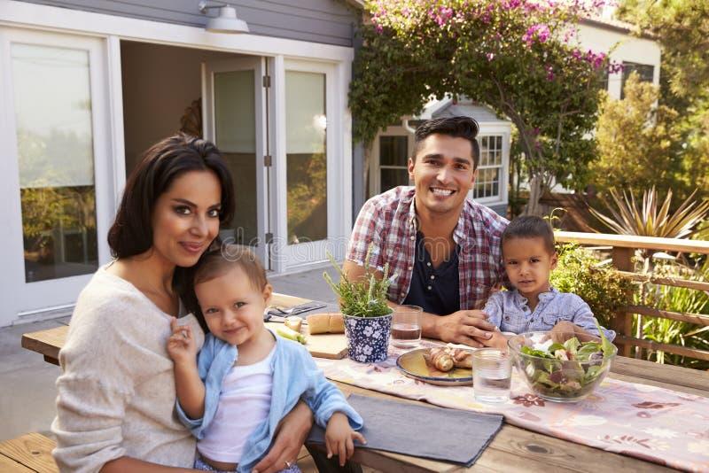 Portret van Familie die thuis Openluchtmaaltijd in Tuin eten royalty-vrije stock afbeeldingen