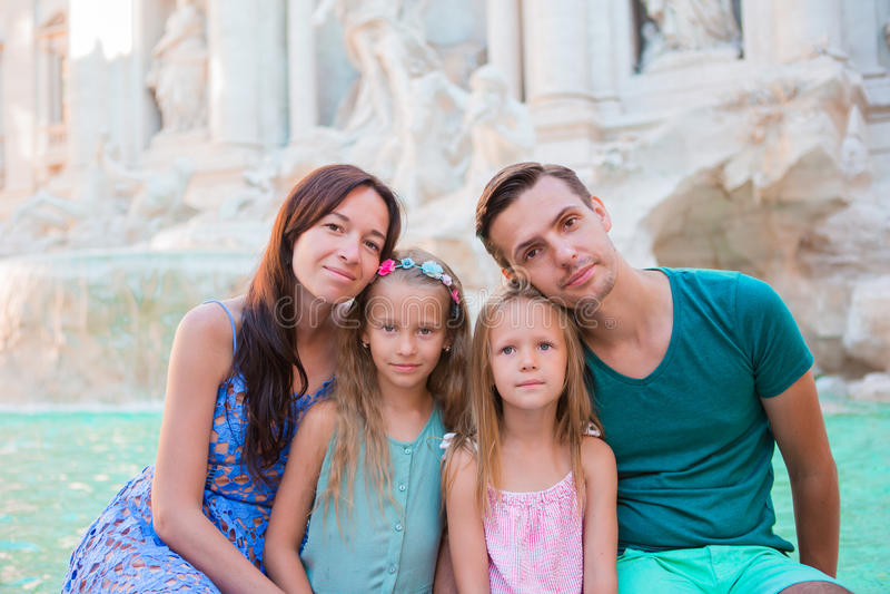Portret van familie in Fontana Di Trevi, Rome, Italië De gelukkige ouders en de jonge geitjes genieten van Italiaanse vakantievak royalty-vrije stock afbeelding