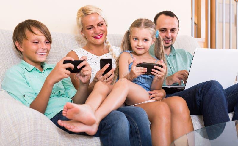 Portret van familie het spelen met gadgets thuis stock afbeeldingen
