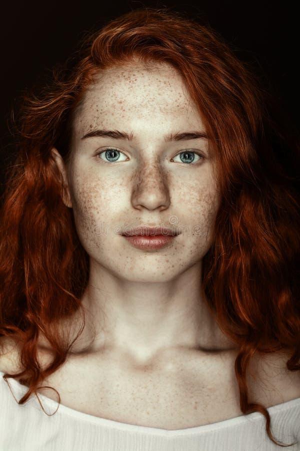Portret van freckled roodharigevrouw die camera bekijken royalty-vrije stock afbeeldingen