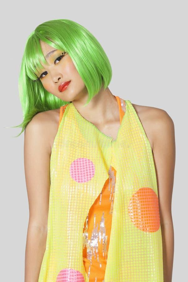 Portret van funky jonge vrouw met groen haar die zich tegen grijze achtergrond bevinden royalty-vrije stock afbeelding