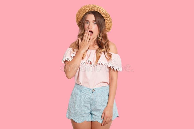 Portret van geïmponeerd verrast die model over roze achtergrond in studio wordt geïsoleerd, die haar mond behandelen met hand, di stock afbeeldingen