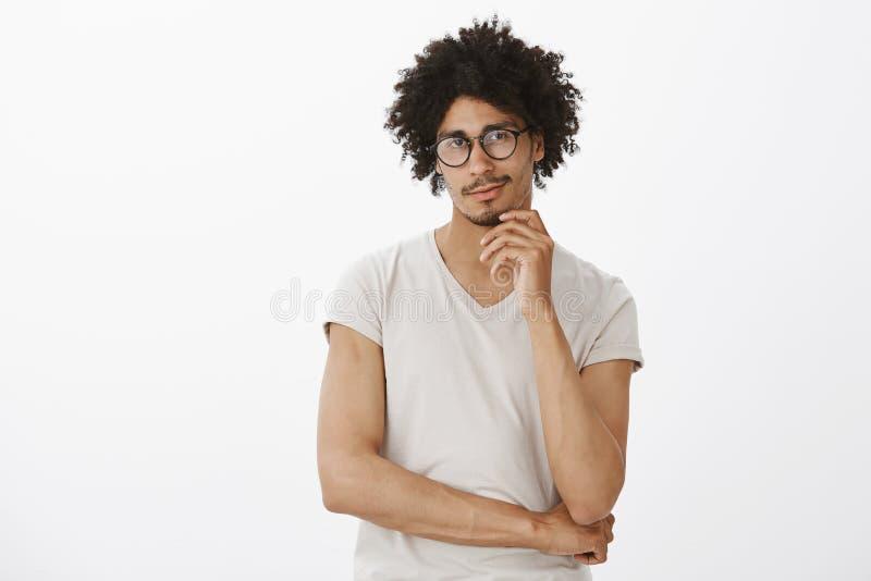 Portret van geïntrigeerde charmante Spaanse kerel in glazen en t-shirt, die en wat betreft kin, die bij camera staren met smirkin royalty-vrije stock afbeeldingen