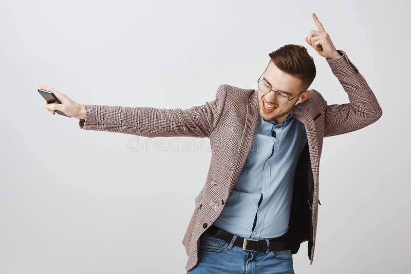 Portret van geamuseerde gelukkige knappe jonge mannelijke ondernemer in jasje en glazen het dansen het schuddende handen houden royalty-vrije stock fotografie