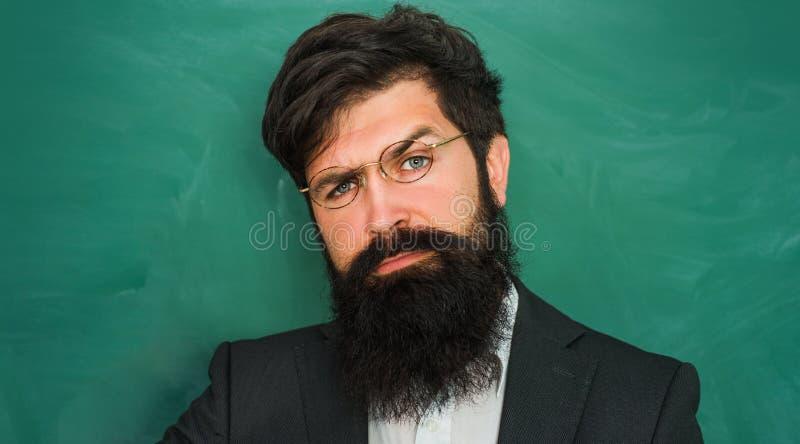 Portret van gebaarde professor bij schoolles bij bureaus in klaslokaal - sluit omhoog Professor in klasse op bord royalty-vrije stock afbeeldingen