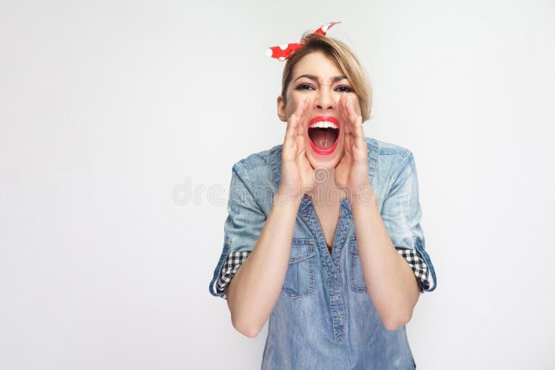 Portret van gebrul mooie jonge vrouw in toevallig blauw en of denimoverhemd, make-up en rode hoofdband die schreeuwen gillen bevi royalty-vrije stock fotografie