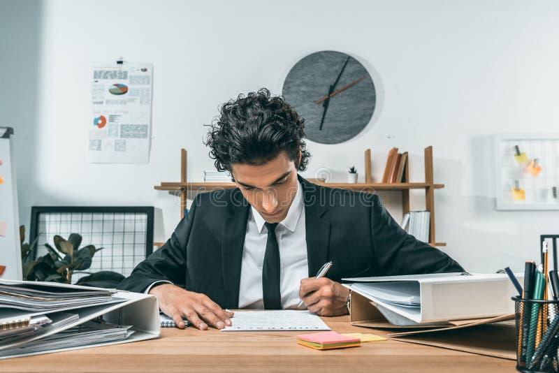 portret van geconcentreerd zakenman het schrijven werkplan op het werk royalty-vrije stock foto's