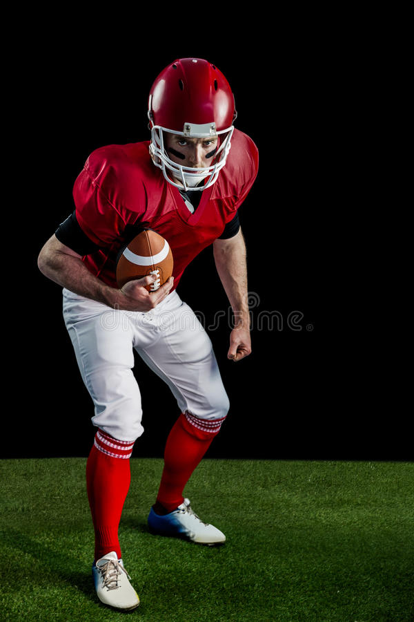 Portret van geconcentreerde Amerikaanse voetbalster die bereid aan te vallen zijn stock foto